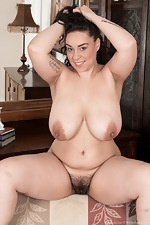 The busty Anastasia Lux strips naked by her sofa  - pic #15