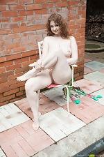 Bazhena strips naked in her outside garden  - pic #9