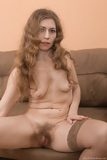 Elza strips naked on her brown couch looking sexy  - pic #9