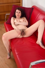 Emily Winters strips naked on her red sofa - pic #12