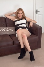 Ethel strips naked on her brown sofa  - pic #1