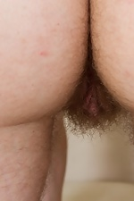 Mary strips on her couch, fondles her hairy pussy - pic #12