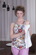 Philippa strips nude by her dining room table - pic #1