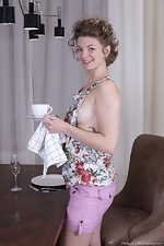 Philippa strips nude by her dining room table - pic #2