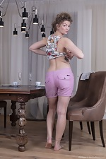 Philippa strips nude by her dining room table - pic #3