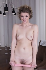 Philippa strips nude by her dining room table - pic #6