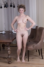 Philippa strips nude by her dining room table - pic #7
