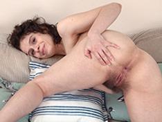 Sabrina Eve strips naked on her beige sofa