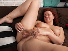Ranunculus strips nude on her brown couch