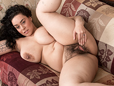 The busty Anastasia Lux strips naked by her sofa