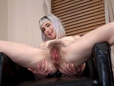 Esme strips naked on her black armchair